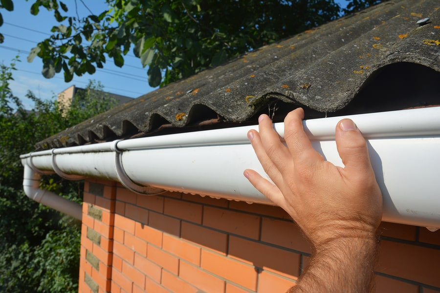 checking home gutter for any debris or chokes